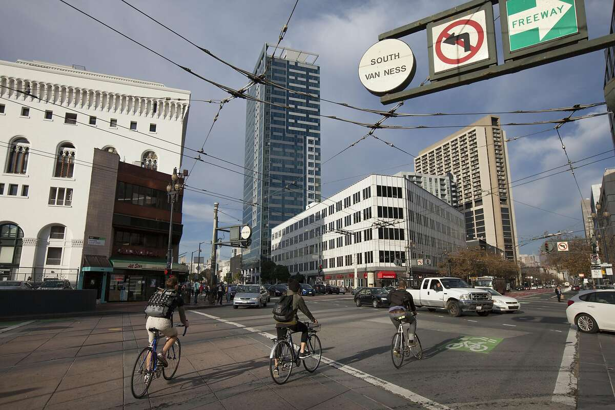 Bicyclists ride down Market Street, Saturday, Nov. 21, 2015, in San Francisco, Calif. The city has agreed to sell lots near Market Street and Van Ness Avenue to a housing developer, the latest in a series of large housing projects planned for the area. The cafe building on the left and 30 Van Ness Avenue on the right will be sold.