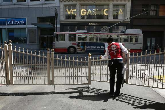 Union Square hospitality ambassador Tona Brown closes the gate for Maiden Lane at Stockton Street as vehicles are prohibited after 11am on Tuesday, September 6, 2016, in San Francisco, Calif.