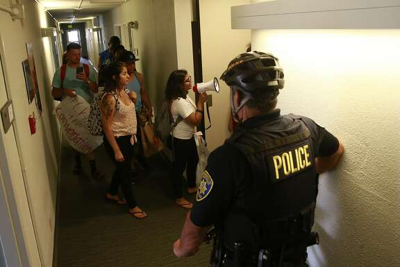UC Berkeley police keep watch as UC Berkeley students protest against former law dean Sujit Choudhry who still has an office in the Berkeley Law building in Berkeley, Calif., as seen on Wed. Sept. 7, 2016. Choudhry has nothing to teach and has been barred since last semester after he stepped down.