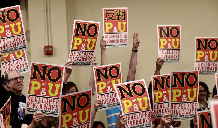 Community members hold their campaign signs high as San Francisco tenants, leaders of tenants, labor, non-profit housing and faith organizations hold a No on propositions P and U rally at Glide Memorial Church in San Francisco, Calif., on Wed. Sept. 7, 2016.