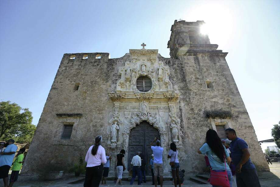 Guests walk past and take photos in front of the Mission San Jose chapel after the World Heritage Inscription Ceremony on Saturday, Oct. 17, 2015. Hundreds of guests and the public watched as young mariachis from Harlandale Independent School District performed as well as watched ceremonies conducted by two Indigenous groups. The whole affair was highlighted by the unveiling of a plaque that will be displayed at San Jose to mark the new World Heritage designation for all five of the missions around the city.  (Kin Man Hui/San Antonio Express-News) Photo: Kin Man Hui, Staff / San Antonio Express-News / ©2015 San Antonio Express-News