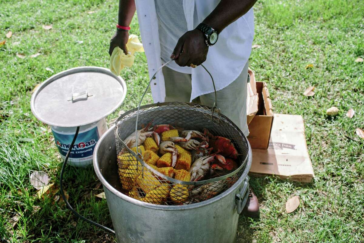 Michael Moten checks the progress of crabs and corn boiling during a family cookout at City Park in New Orleans.