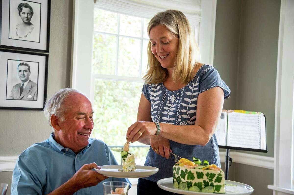 Sarah Gannholm serves smorgastarta, an elaborate Swedish savory sandwich cake, to her father Geoffrey Chick in Seattle.
