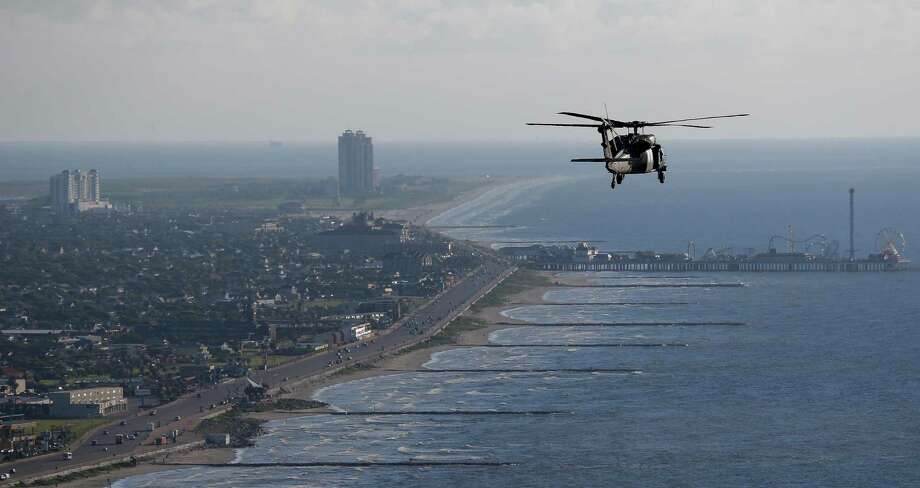 "An Army Black Hawk helicopter, carrying U.S. Army Corps of Engineers officials, flies over Galveston while looking at FEMA Debris Sites, temporary housing and rehabilitation considerations while on a tour of the Corps current and proposed projects on September 7, 2016. A dike, called the ""Ike Dike,"" is being proposed to protect Galveston, Bolivar and the Galveston Bay area from storm surges. Photo: Michael Ciaglo, Houston Chronicle / © 2016  Houston Chronicle"