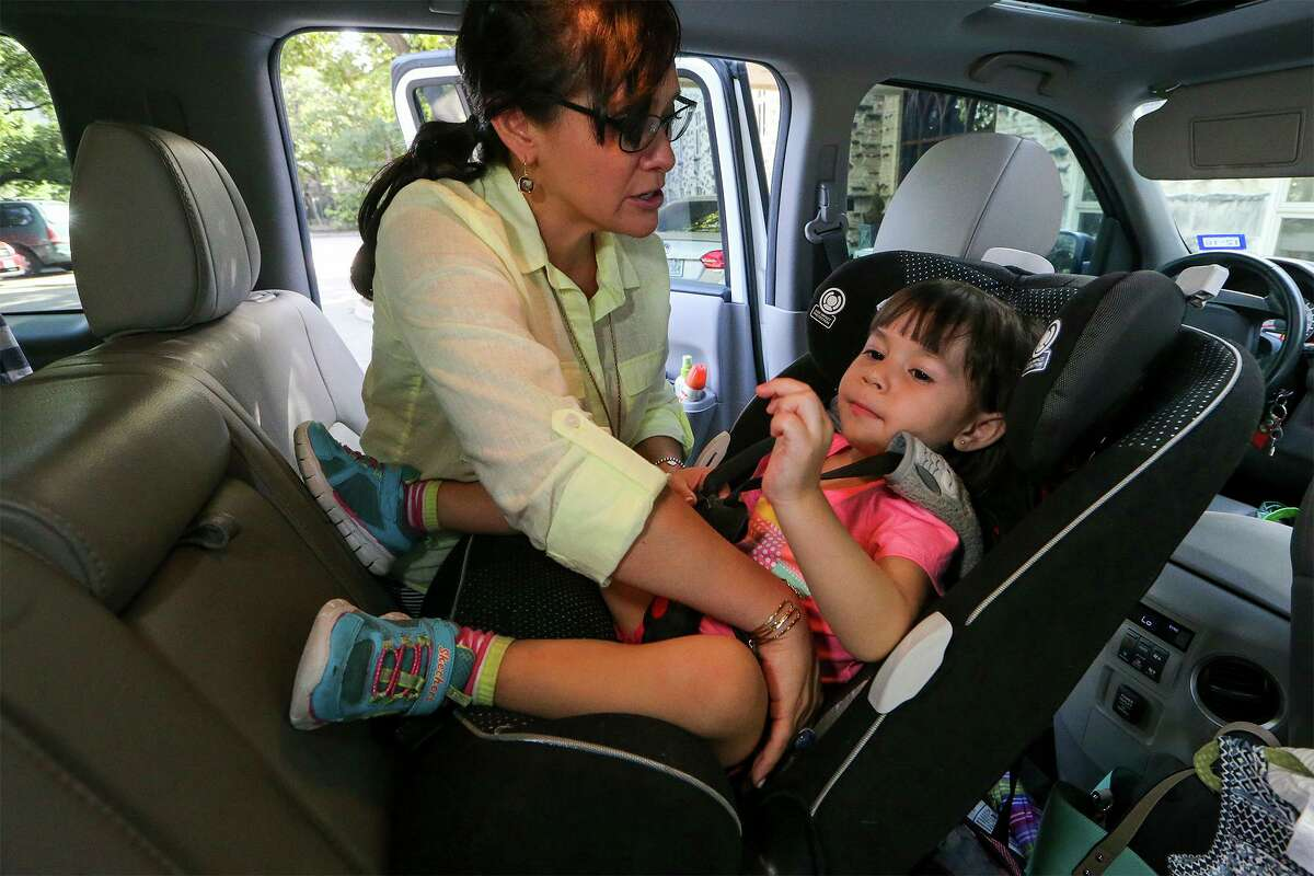 In this 2016 photo, Henrietta Munoz buckles her daughter into a rear-facing car seat. Experts say this is a best practice. Gov. Greg Abbott vetoed legislation that would have mandated it for children 2 years and younger.