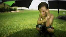 Roanin Walker, 7, waits for the sprinklers to shower him during a hot day on the front yard of his parents home in Kingwood, Tuesday, July 26, 2016.