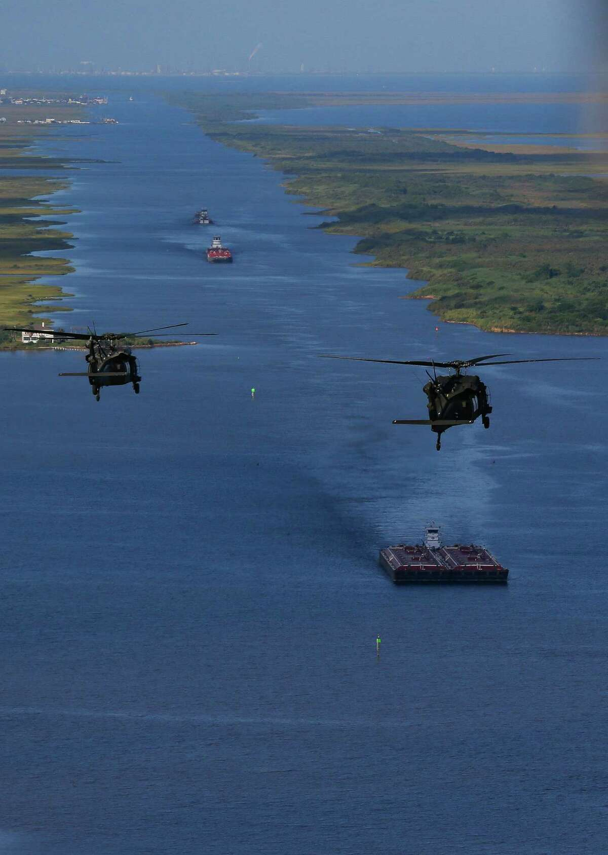 Army Black Hawk helicopters, carrying U.S. Army Corps of Engineers officials, flies over the Bolivar Peninsula Wednesday, September 7, 2016. A dike, called the