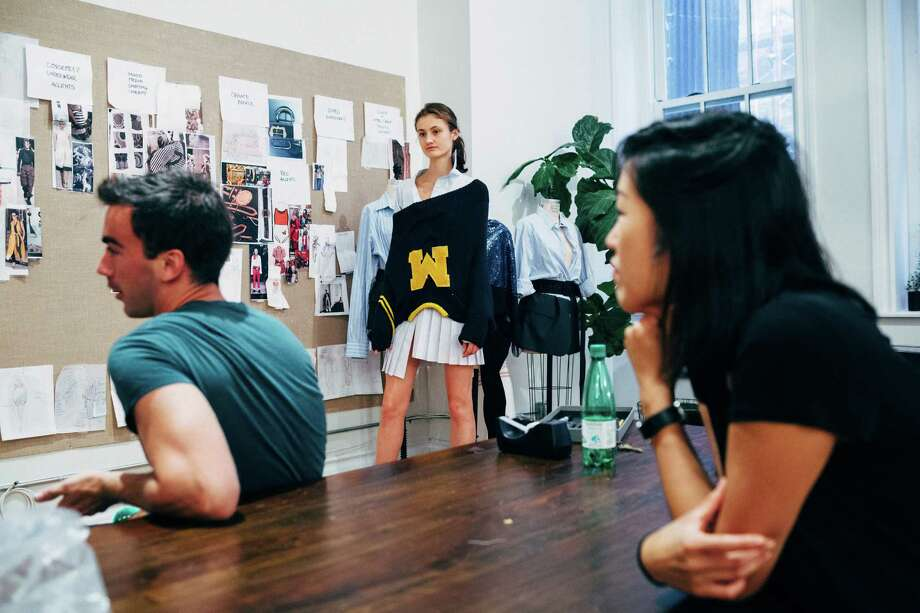 Vik Kukandzina tries on a design at Monse, the fashion studio of Fernando Garcia, left, and Laura Kim, right in Manhattan, Aug. 29, 2016. Garcia and Kim were proteges of the late Oscar de la Renta, but were passed over for an outsider when the fashion icon died; now on their own, their Monse label has become the hottest name in the industry, even before their first full show. (Andrew White/The New York Times)V Photo: ANDREW WHITE, STR / NYTNS