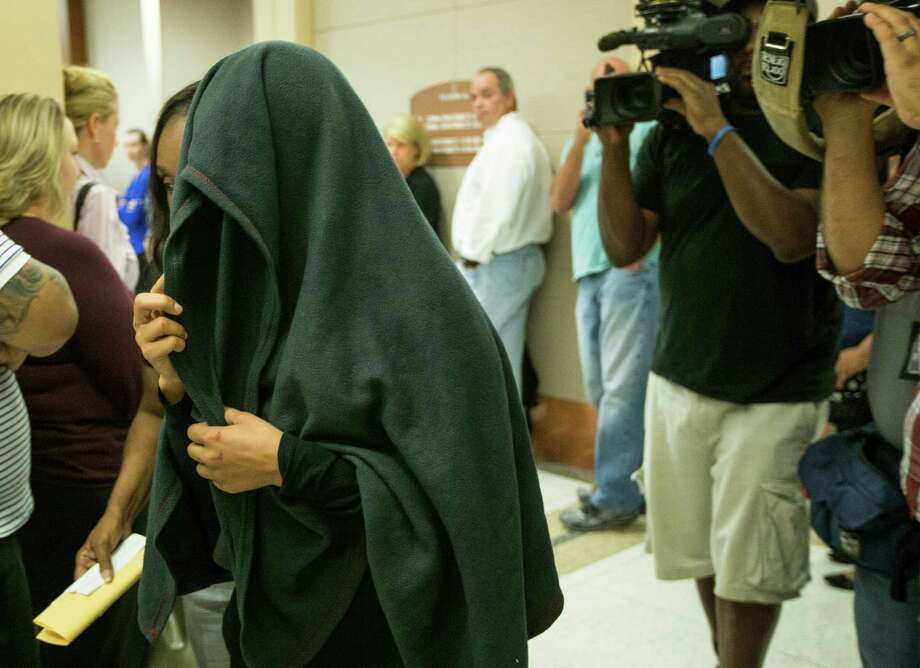 Tuwanna Moore, who is accused of driving drunk and injuring a state trooper, covers her head as she walks out of a Houston courtroom on Wednesday. Photo: Brett Coomer, Staff / © 2016 Houston Chronicle