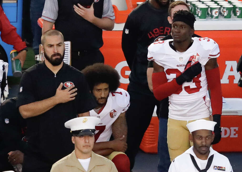 San Francisco 49ers quarterback Colin Kaepernick, middle, kneels during the national anthem before the team's NFL preseason football game against the San Diego Chargers, in San Diego. Photo: Chris Carlson / Copyright 2016 The Associated Press. All rights reserved.
