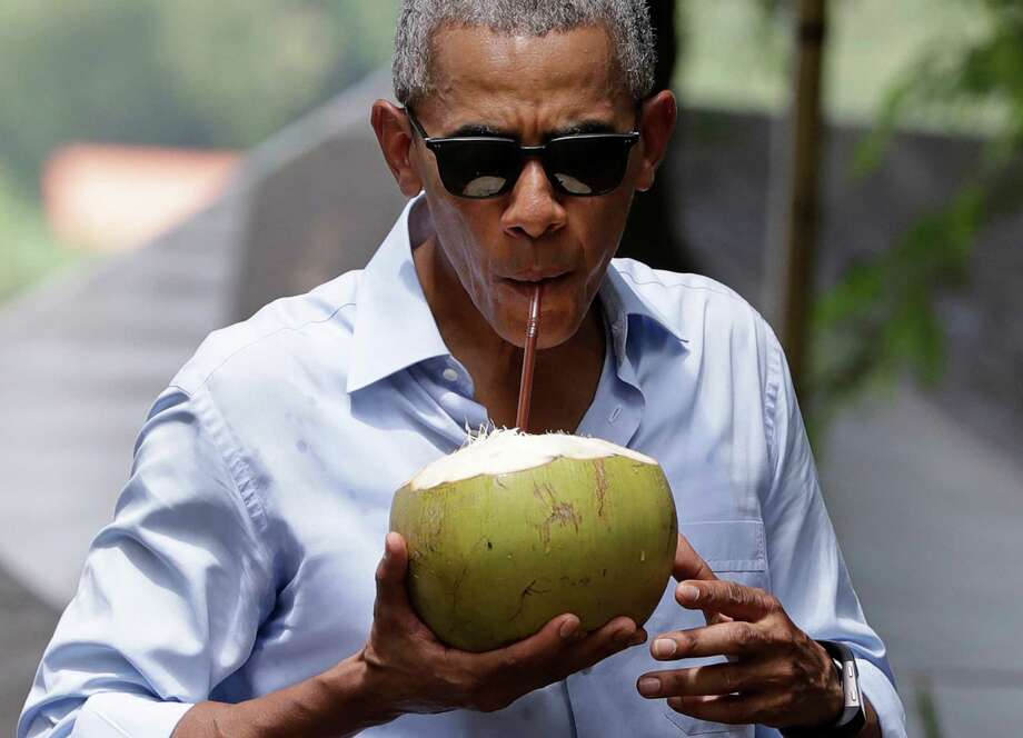 President Barack Obama drinks from a fresh coconut along the banks of the Mekong River in the Luang Prabang, Laos, on Wednesday. Photo: Carolyn Kaster, STF / Copyright 2016 The Associated Press. All rights reserved.