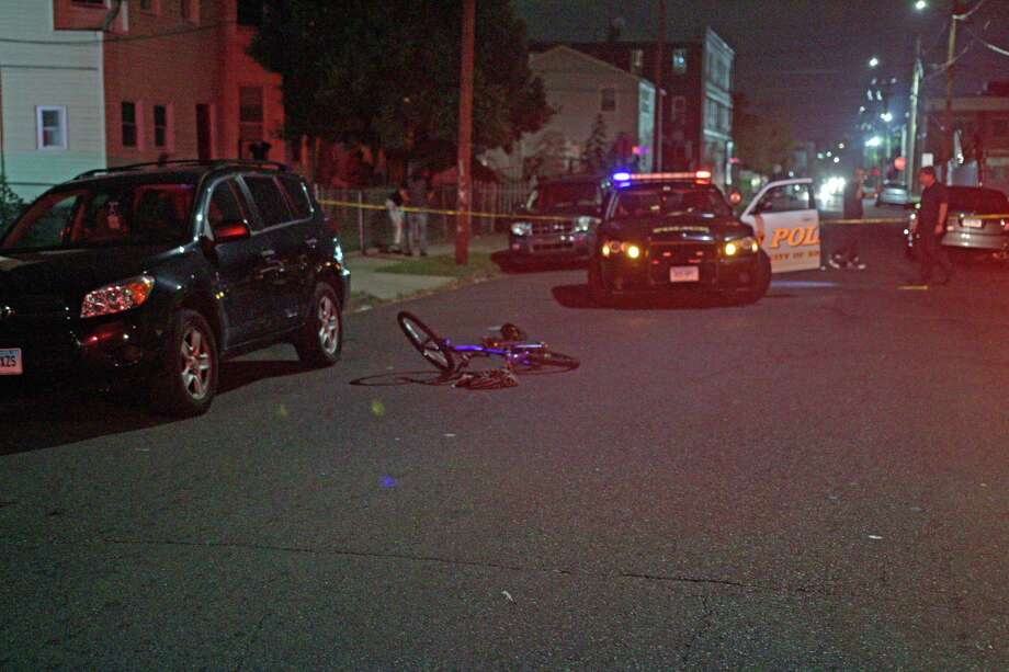 As police investigate a shooting Wednesday night near the corner of Maple and Kossuth streets in Bridgeport, Conn. a bicycle the victim had been riding before he was shot lies in the road on Sept. 7, 2016. Photo: Cedar Attanasio, Hearst Connecticut Media / Connecticut Post