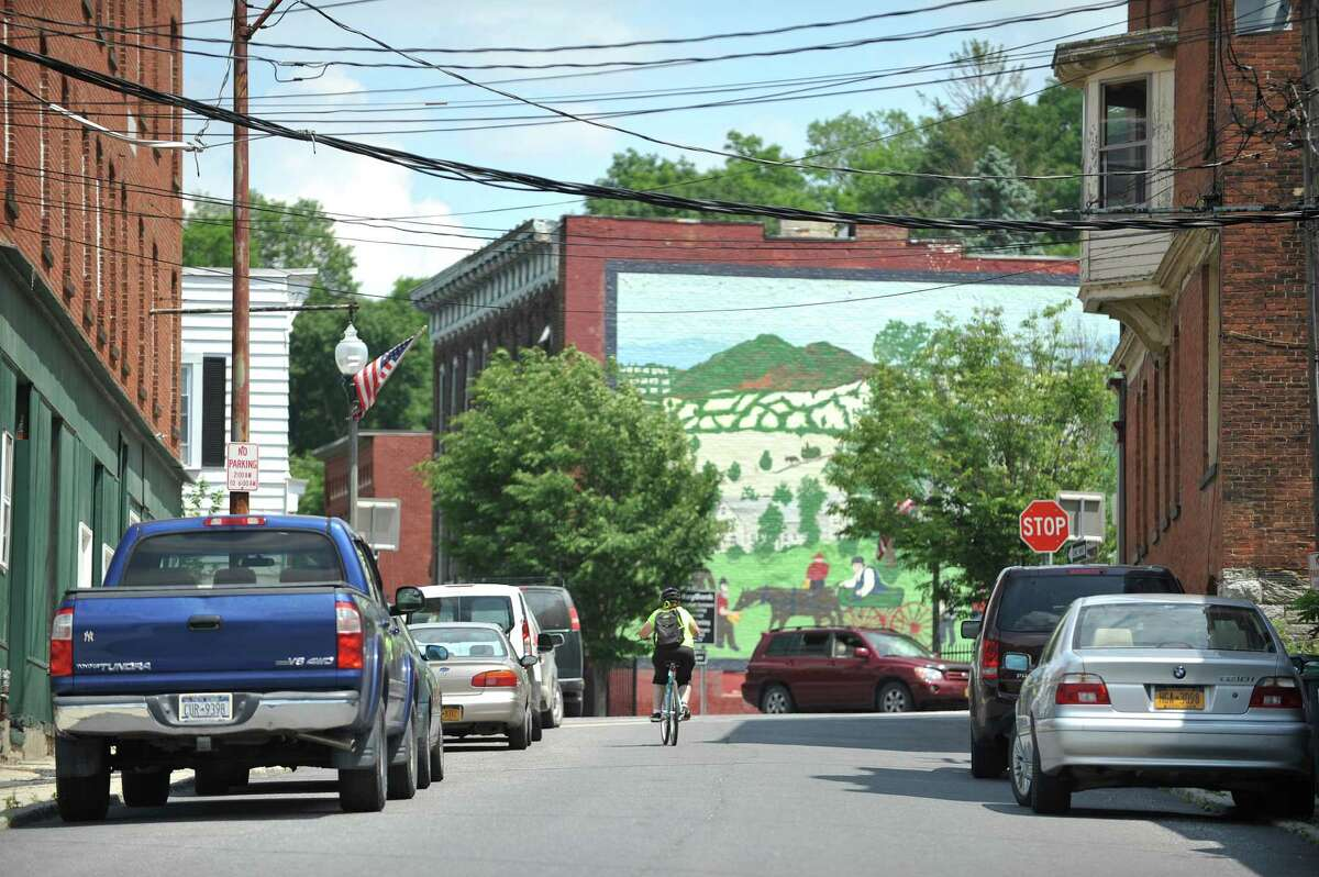 A woman rides a bicycle along Classic Street on Tuesday, June 28, 2016, in Hoosick Falls, N.Y. (Paul Buckowski / Times Union)