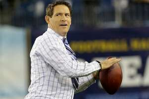 Hall of Fame quarterback and ESPN announcer Steve Young throws a football before an NFL football game between the Tennessee Titans and the New York Jets on Monday, Dec. 17, 2012, in Nashville, Tenn. Young played for the San Francisco 49ers and the Tampa Bay Buccaneers.