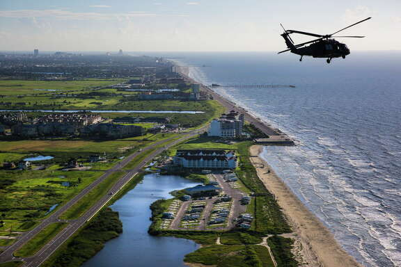 An Army Black Hawk helicopter, carrying U.S. Army Corps of Engineers officials, flies past the end of the seawall and over Galveston while looking at FEMA Debris Sites, temporary housing and rehabilitation considerations while on a tour of the Corps current and proposed projects Wednesday, September 7, 2016.