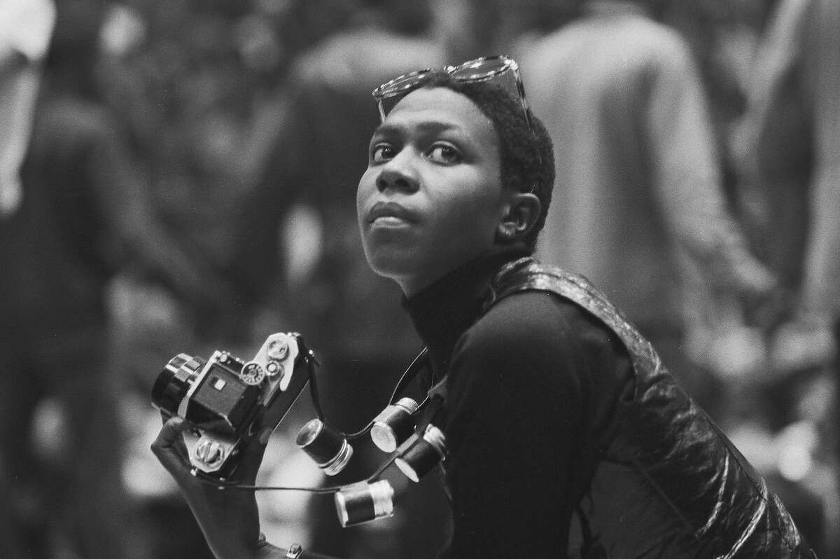 Political and social activist and Black Panther member Afeni Shakur looks up while photographing the scene during a rally in support of the Panther 21, New York, New York, April 4, 1970. The Panther 21 were Black Panther members arrested by New York police under suspicion of planning a series of bombings, charges that were eventually dropped against all the defendents. (Photo by David Fenton/Getty Images)