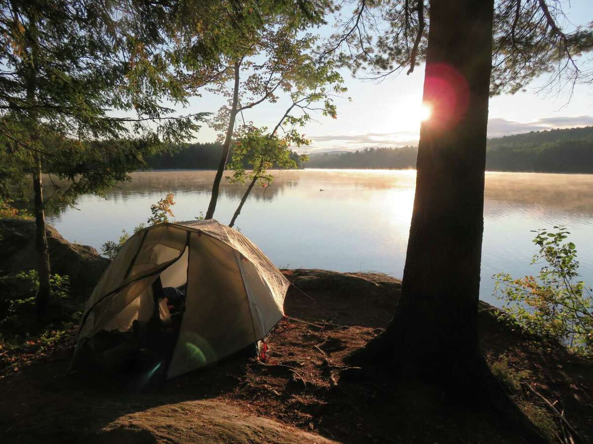 The early morning sun hits a tent at a remote campsite at the Putnam Pond State Campground in Chilson. (Herb Terns / Times Union)