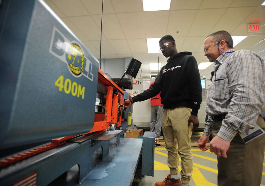 Bassick High School junior Arcadius Takinda, 17, left, cuts a round from a cylinder of aluminum under the direction of instructor Joe Duhaime in his manufacturing class at Housatonic Community College in Bridgeport, Conn. on Thursday, April 28, 2016. The college has partnered with the Bridgeport high school to allow a select group of students to start taking classes in the advanced manufacturing program. Photo: Brian A. Pounds / Hearst Connecticut Media / Connecticut Post