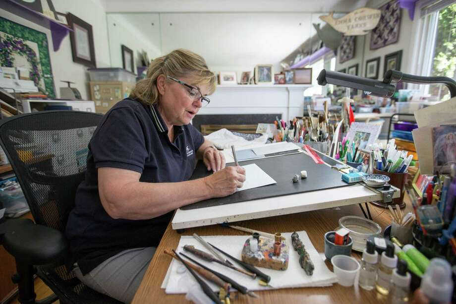 Vicki Corwin, 61, an independent calligrapher, works out of the living room she converted into an art studio at her home on Aug. 8, 2016 in Royal Oak, Mich. Corwin uses a pointed pen split nib to write her calligraphy and is a member of the International Association of Master Penmen, Engrossers and Teachers of Handwriting. Photo: Kimberly P. Mitchell /Detroit Free Press / Detroit Free Press