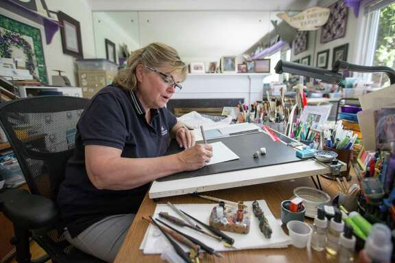 Vicki Corwin, 61, an independent calligrapher, works out of the living room she converted into an art studio at her home on Aug. 8, 2016 in Royal Oak, Mich. Corwin uses a pointed pen split nib to write her calligraphy and is a member of the International Association of Master Penmen, Engrossers and Teachers of Handwriting.
