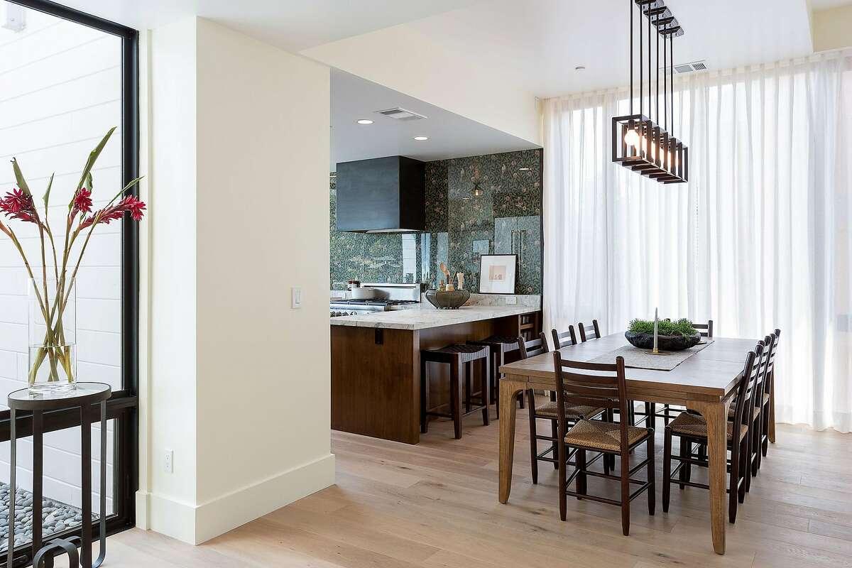 Modern pendant lights illuminate the open dining area.