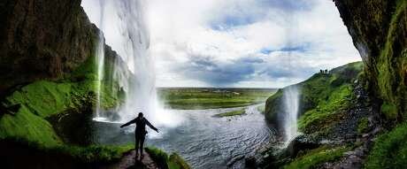 Water cascades almost 200 feet off the cliff at Seljalandsfoss as visitors get a full circle view of the waterfall with a hike into a cave behind the falls in southern Iceland.