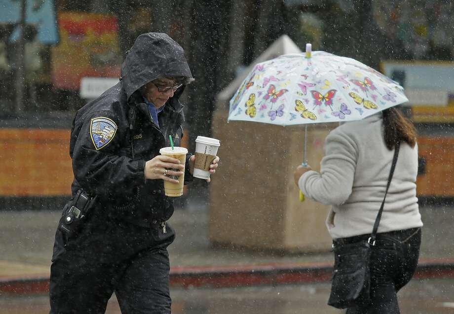 Two women take cover from the rain in Sausalito in March. Forecasters doubt the dry weather pattern known as La Niña will make an appearance this winter. Photo: Eric Risberg, AP