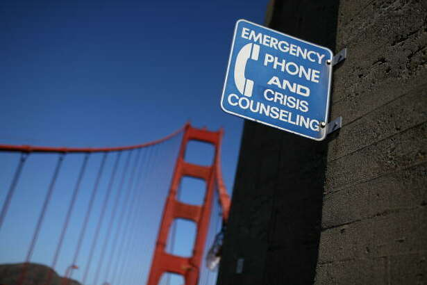 SAN FRANCISCO - OCTOBER 10:  A sign for an emergency phone is seen on the span of the Golden Gate Bridge October 10, 2008 in San Francisco, California. The Golden Gate Bridge District board of directors voted today to continue with a plan to build a suicide prevention net on the world famous bridge with a price tag of $40 to $50 million dollars. An estimated 1,300 people are believed to have jumped to their death from the bridge since it was opened in 1937.  (Photo by Justin Sullivan/Getty Images)