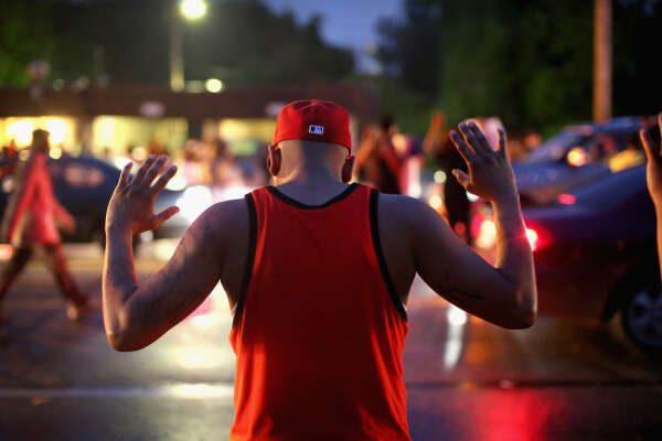"""FERGUSON, MO - AUGUST 15:  Demonstrators gather along West Florissant Avenue to protest the shooting of Michael Brown on August 15, 2014 in Ferguson, Missouri. Brown was shot and killed by a Ferguson police officer on August 9. Protestors raise their hands and chant """"Hands up, don't shoot""""  as a rally cry to draw attention to reports that stated Brown's hands were raised when he was shot. Tonight demonstration again ended with protestors  clashing with police followed by more looting.  (Photo by Scott Olson/Getty Images)"""