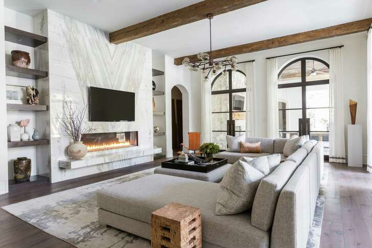 Above: Slabs of marble create natural artwork on the main wall of the living room. Below: Chrome pendant lights, dazzling faucets and a hammered-nickel range hood serve as jewelry in the kitchen.