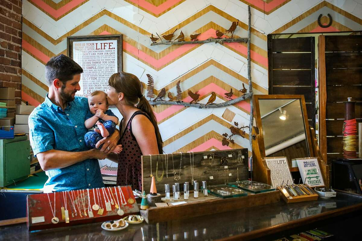 Owners of Bespoke shop Brian Hess (left) and Heather River (right) embrace their son Oberon Hess, 5 months, while posing for a portrait in their store in Truckee, California, on Friday, Sept. 2, 2016.