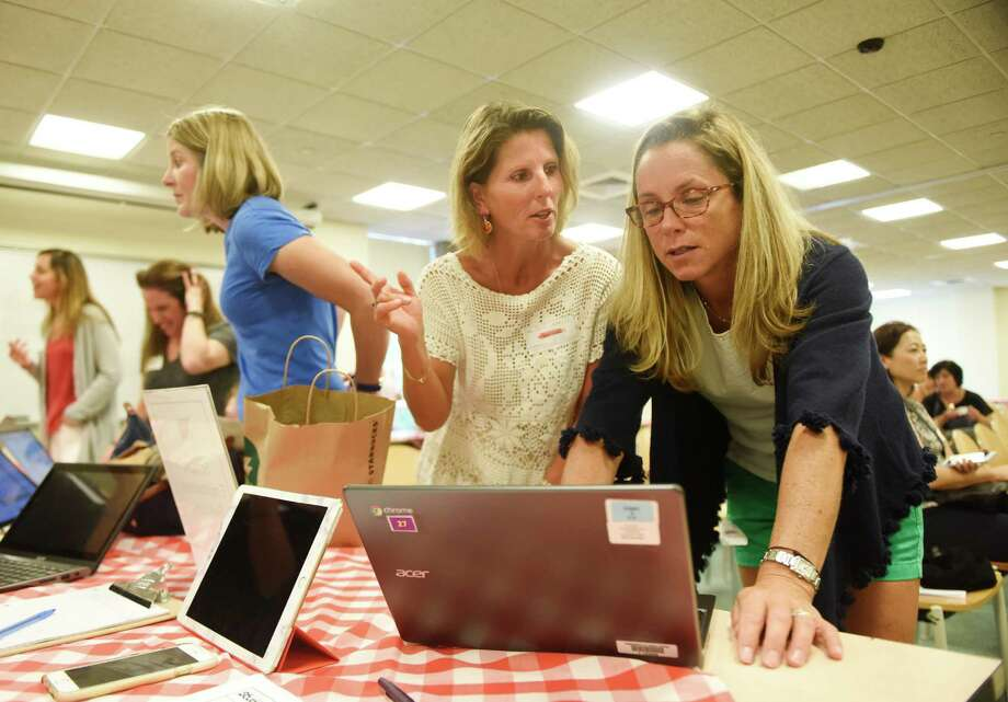 PTA volunteer coordinator Jen Ludington, right, helps Cos Cob resident Daniela Fischer, who has a freshman at GHS, sign up to volunteer before the first PTA meeting of the 2016-2017 school year in the Greenwich High School media center in Greenwich, Conn. Thursday, Sept. 8, 2016. PTA members were given the chance to sign up for different volunteer activities at the volunteer fair. Following the volunteer fair, there were short presentations by innovation lab teacher and GPS Distinguished Teacher of the Year Dr. Sarah Goldin, Interim Superintendent of Schools Dr. Sal Corda and GHS Headmaster Dr. Chris Winters. Photo: Tyler Sizemore / Hearst Connecticut Media / Greenwich Time