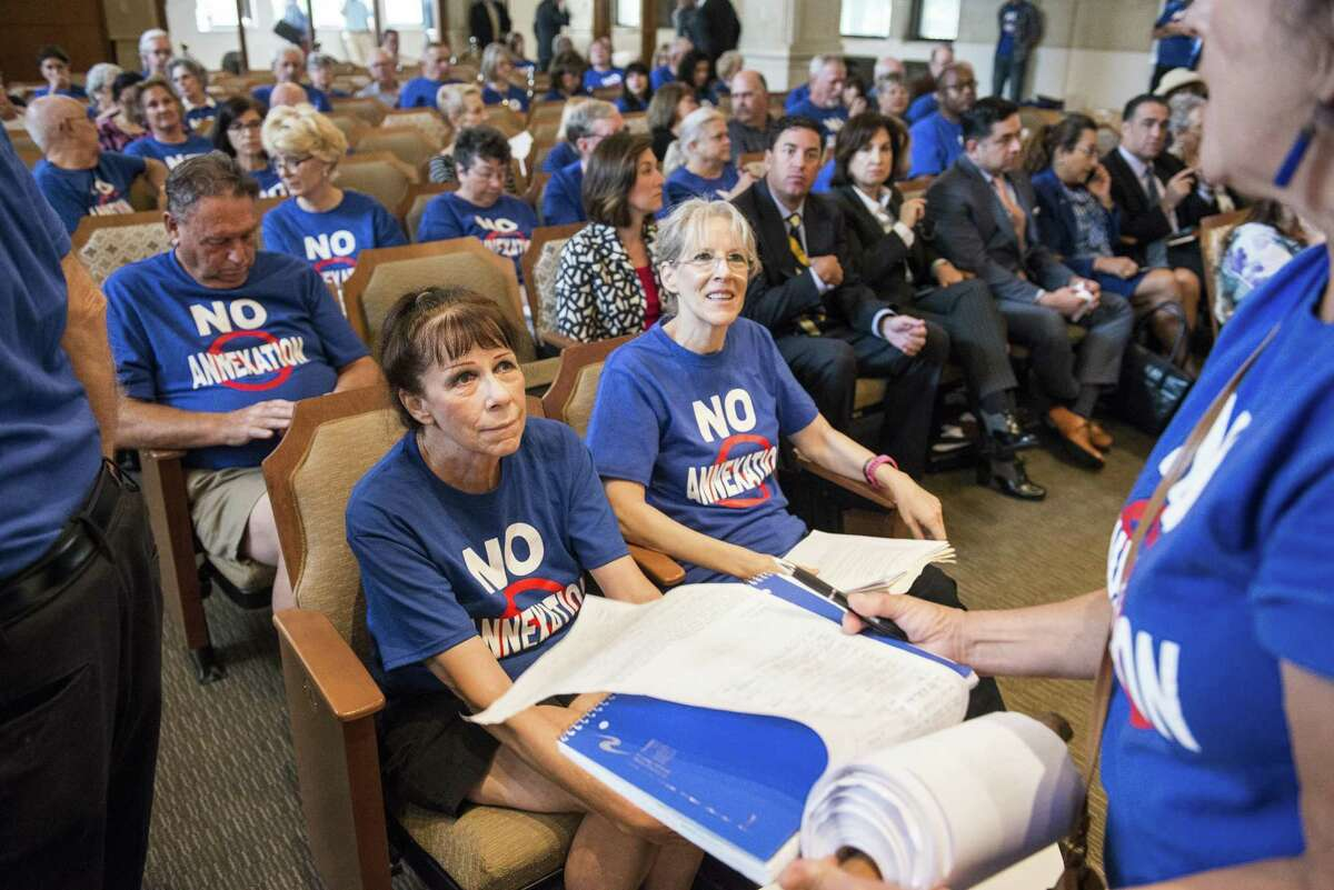 """Sisters Kimberly Vogel, left, and Susan Vogel, right, wearing """"No Annexation"""" t-shirts, sit in the front row during a San Antonio City Council meeting where they voted on whether to annex several parts of unincorporated Bexar County, notable a 15-square mile area along Interstate 10 West, on Thursday, September 8, 2016 in San Antonio, Texas."""