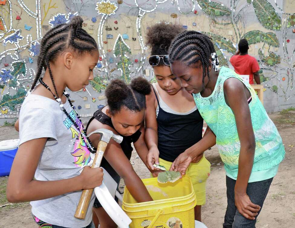 Neighborhood children, from left, Natalia Johnson, 9, Naviana Everett, 7, Nevaeh Everett, 9 and Maliaha Friar, 11 sort through pieces of tiles for a mosaic mural on the side of the Community Loan Fund building at 255 Orange Street on Saturday, July 16, 2016, in Albany, N.Y. The mural will be unveiled at 5:30 p.m. Friday near Sheridan Hollow Commons. (John Carl D'Annibale / Times Union) (John Carl D'Annibale / Times Union)