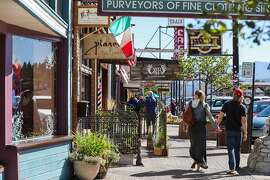 People walk past shops in downtown Truckee, California, on Friday, Sept. 2, 2016.