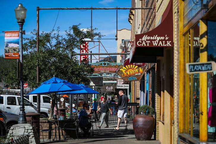 People walk by shops in downtown Truckee in Truckee, California, on Friday, Sept. 2, 2016.