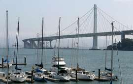 Sailboats are moored at the Clipper Cove marina on Treasure Island in front of the new Bay Bridge span in San Francisco, Calif. on Sept. 8, 2016. Unexpected repair work and other expenses have nearly exhausted a contingency account for the new bridge.