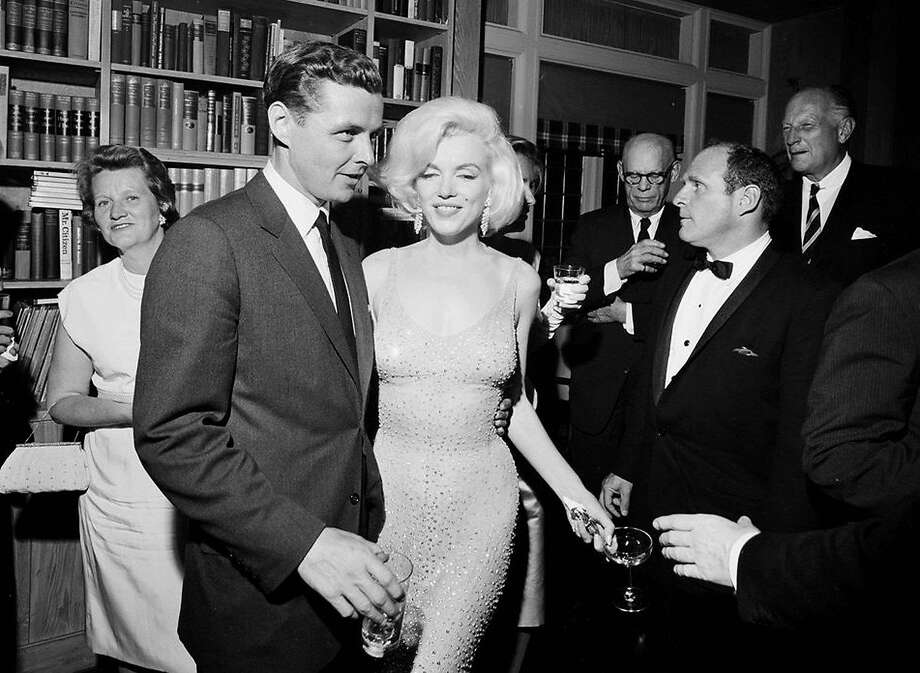 "In this May 19, 1962 photo provided by the John F. Kennedy Presidential Library and Museum, actress Marilyn Monroe wears the iconic gown that she wore while singing ""Happy Birthday"" to President John F. Kennedy at Madison Square Garden, during a reception in New York City. Standing next to Monroe is Steve Smith, President Kennedy's brother-in-law. J Photo: Cecil Stoughton, Associated Press"