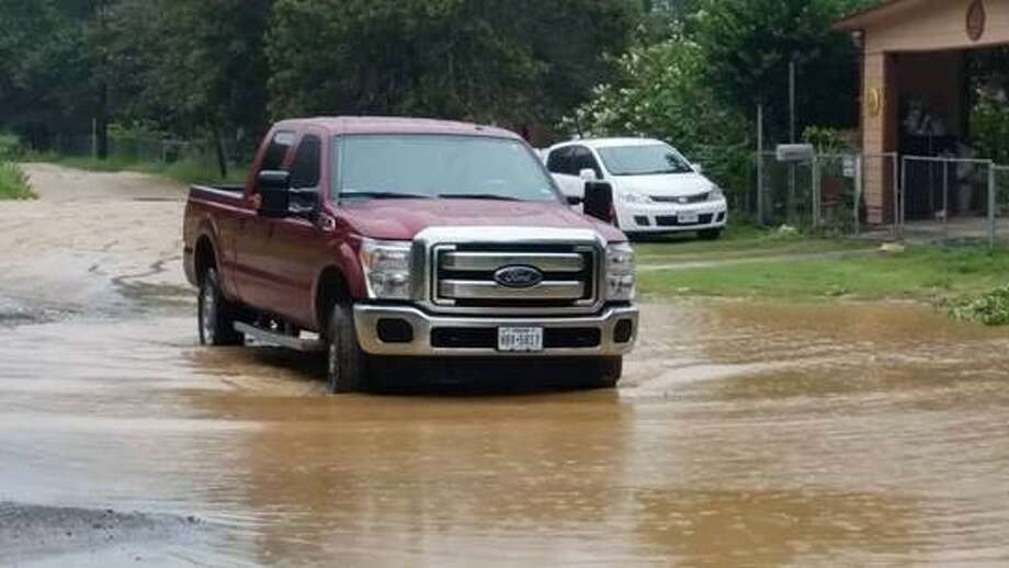 A pickup navigates through a flooded dirt street in Highland Oaks in southern Bexar County on the first day of school last month. Residents in this community have dealt with colonia-like conditions for decades. Photo: /
