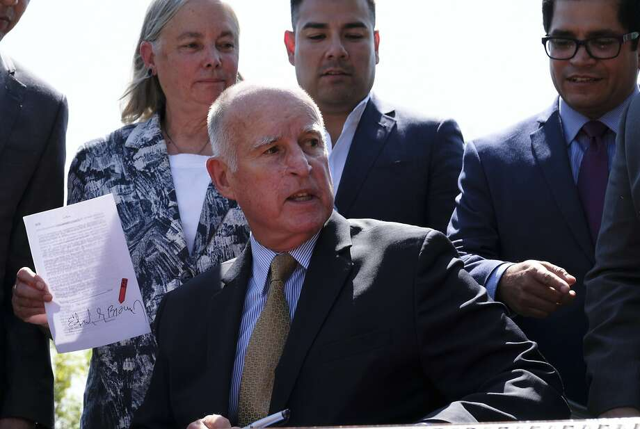 State Sen. Fran Pavley (left), D-Agoura Hills, holds her climate bill after it was signed by Gov. Jerry Brown. She also wrote California's 2006 landmark law on global warming. Photo: Richard Vogel, Associated Press