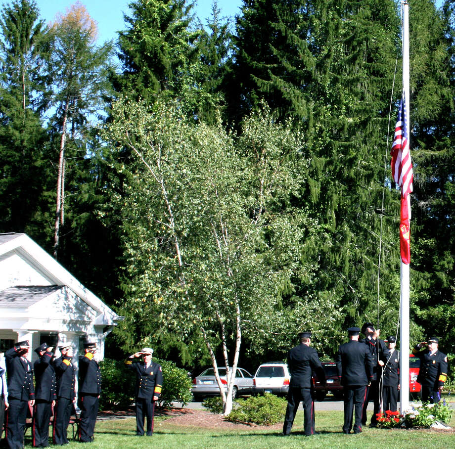 SPECTRUM/Members of the Washington Volunteer Fire Department raise new flags to half staff during  the recent Sept. 11 commemorative service. It has become a department tradition to have this service and hold a  blood drive to recognize the day as a way of support and caring for those who were lost on that day.  Courtesy of the Washington Volunteer Fire Department Photo: ST