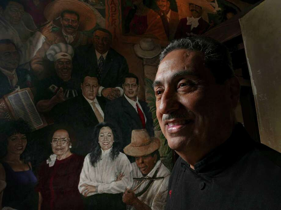 Chef Raul Salazar of Mi Tierra restaurant each day carefully measures out the spices to be used in preparing the various dishes served at the San Antonio landmark. He also mingles with celebrities in the mural. Photo: Billy Calzada /San Antonio Express-News / San Antonio Express-News