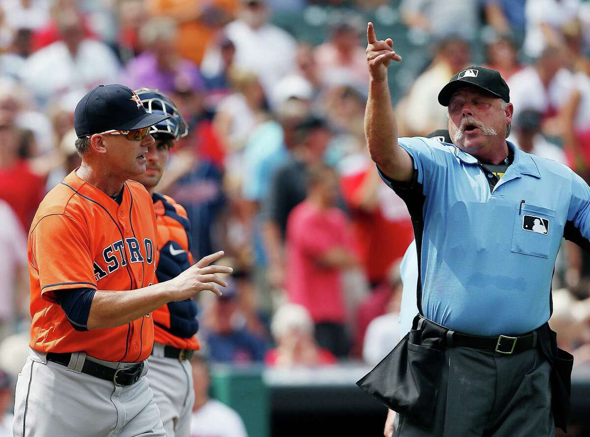 Houston Astros manager A.J. Hinch (14) is ejected from the game by home plate umpire Jim Joyce as catcher Jason Castro looks on after arguing a call that allowed two runs to score on a wild pitch during the third inning of a baseball game against the Cleveland Indians, Thursday, Sept. 8, 2016, in Cleveland. (AP Photo/Ron Schwane)