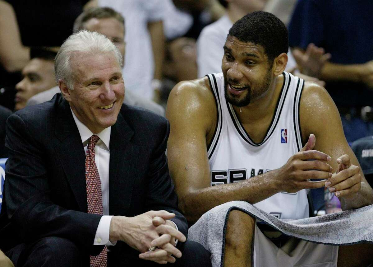 FILE - In this April 5, 2007, file photo, San Antonio Spurs forward Tim Duncan (21) talks with Spurs coach Gregg Popovich, left, during the fourth quarter of their NBA basketball game against the Phoenix Suns in San Antonio. (AP Photo/Eric Gay, File)