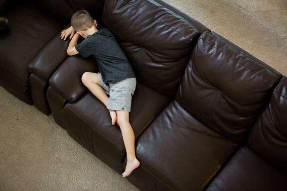 Roanin Walker, 7, lies on the couch after his mother  corrected him for arguing with his siblings over the use of video games, Thursday, Aug. 11, 2016, in Kingwood. Roanin has been diagnosed with attention deficit disorder, anxiety and sensory processing disorder. His parents decided to pull him out of school to homeschool him after he was denied special education.
