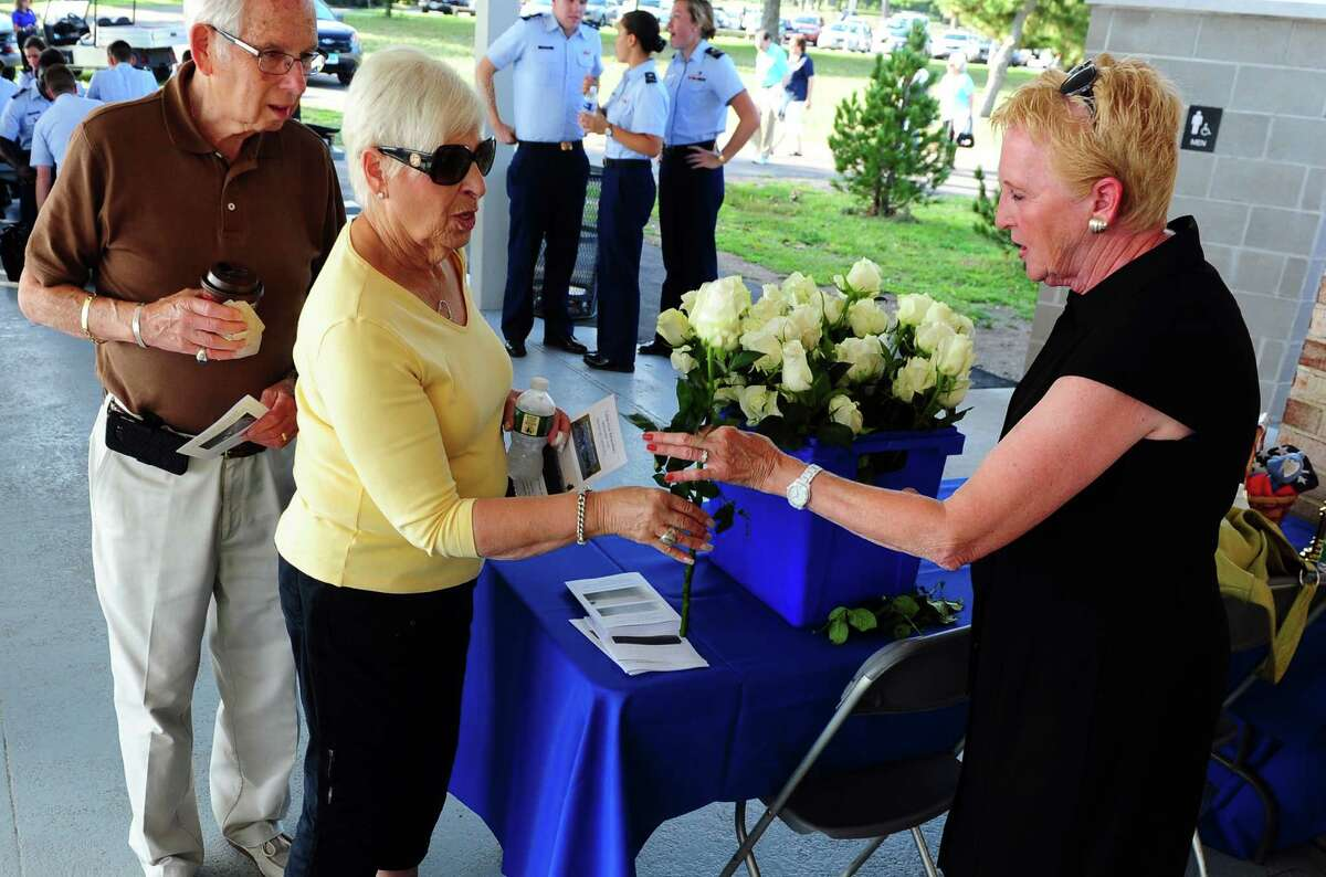 Wilma Wiener, of New Jersey, gets a rose from a volunteer before the start of the Connecticut Remembers September 11th Memorial Ceremony at Sherwood Island State Park in Westport, Conn. on Thursday Sept. 8, 2016. Wilma and her husband Don came for their son Jeffery Wiener, who grew up in Trumbull.