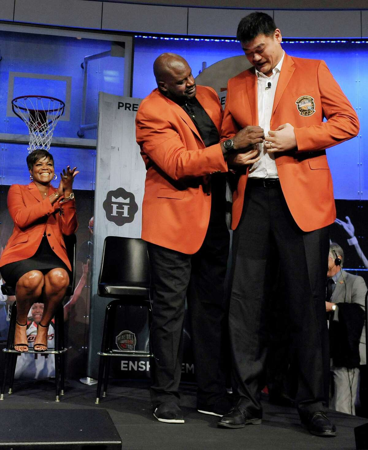 Shaquille O'Neal, left, helps Yao Ming, right, with the fit of his jacket Thursday after the Hall president was unable to scale the heights of Yao's shoulders.