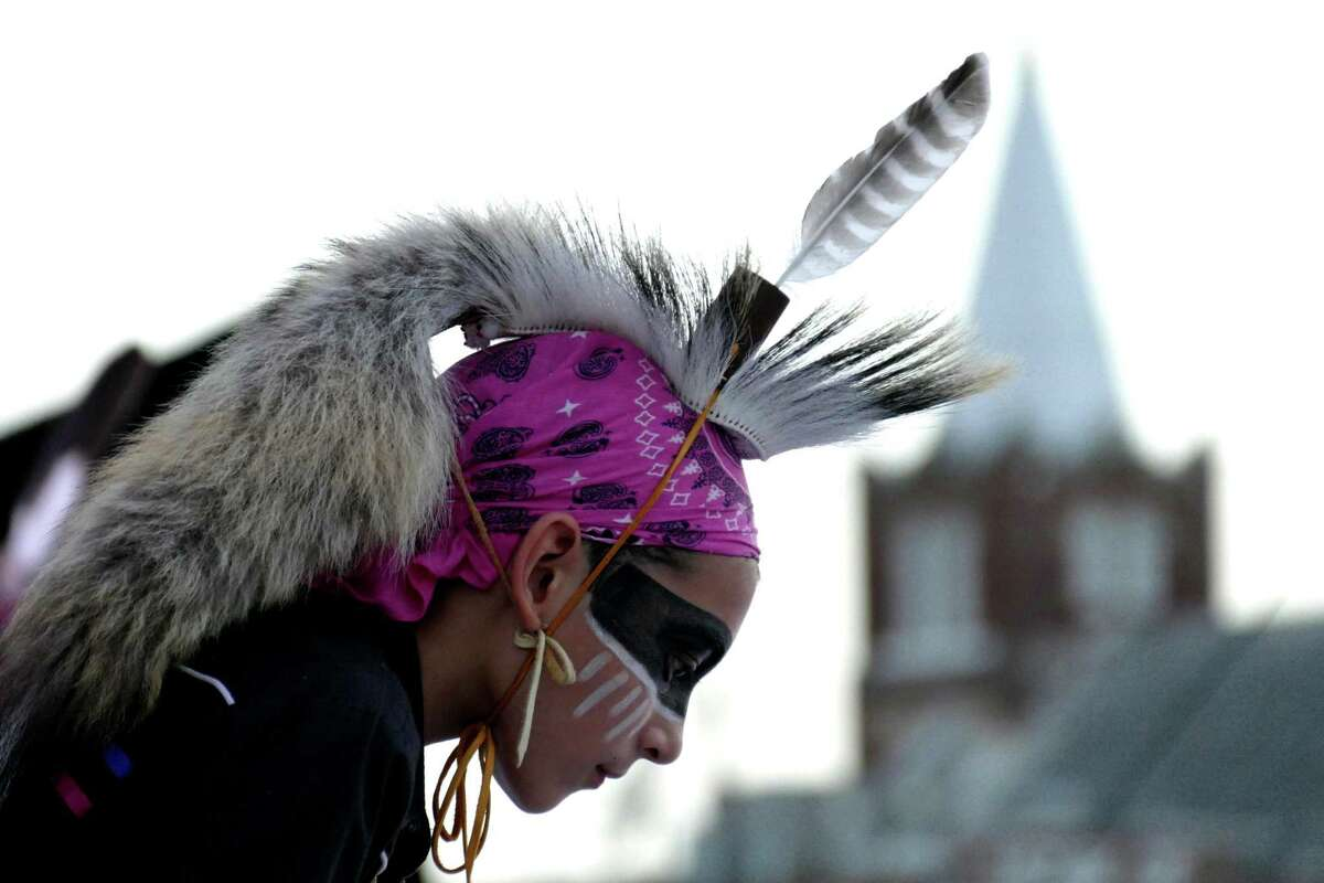 Diego Lopez dances on stage during a tribute to the original Native Americans who lived around San Pedro Creek during the kick-off celebration for the San Pedro Creek Improvements Project near Fox Tech High School on Sept. 8, 2016. In the background is the steeple of San Francesco di Paola Church, at the first site where the Mission San Antonio de Valero is believed to have been for about a year.