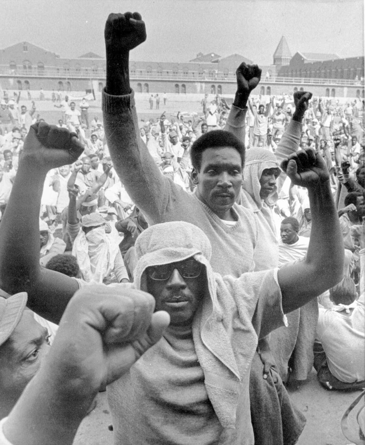 Inmates of Attica state prison in upstate New York raise their fists to show solidarity in their demands during a negotiation session with state prisons Commissioner Russell Oswald, in this Sept. 10, 1971, file photo. (AP Photo/Bob Schutz)