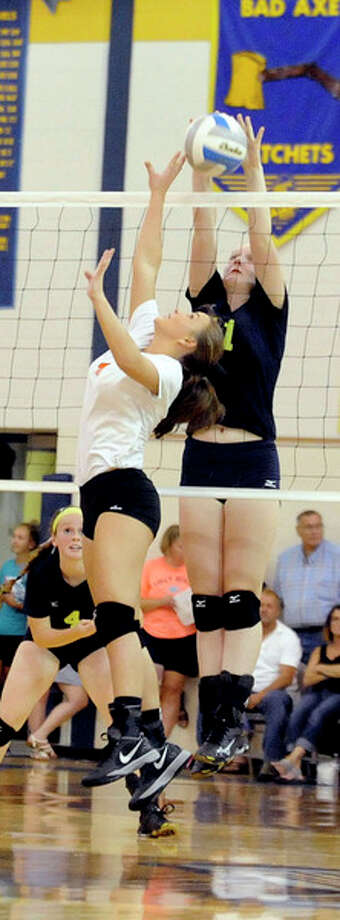 Above, Bad Axe's Emma Cubitt (11) blocks the set of Harbor Beach's Jordan Ryan (4).